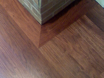 A detail of a wide-width Brazilian Cherry (Jatoba) hardwood floor picture frame around a brick hearth in Coralville