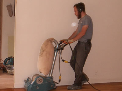 Michael Stalkfleet refinishing a red oak hardwood floor, using a K&T Scorpion sander in Coralville